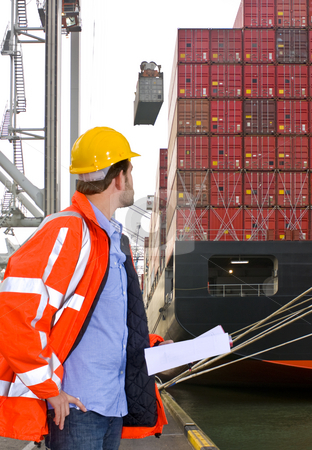 Harbor Inspection stock photo, Harbor employee overseeing the loading of a huge container ship by Corepics VOF