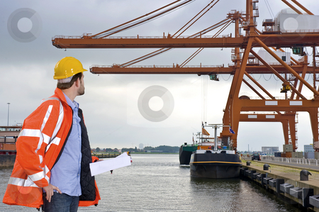 Harbor Inspection stock photo, A man wearing a safety coat and a hard hat inspecting the huge cranes at a container harbor by Corepics VOF