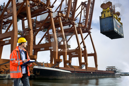 Customs guard stock photo, A customs officr checking containers being unloaded at a commercial harbor by Corepics VOF