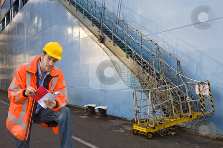 Checking the boardinglist stock photo, A man, wearing a reflective safety coat and a hard hat, ready to check the boarding list with crew names of a huge container ship by Corepics VOF