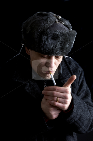 Lighting a Cigarette stock photo, A man, dressed in Soviet attire, lighting a cigarette by Corepics VOF