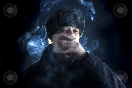 Smoking man stock photo, A man, dressed in a Soviet / Russian attire, smoking a cigarette by Corepics VOF