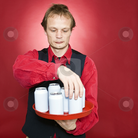 Rearranging cans stock photo, A waiter rearranging beverage cans on his tray by Corepics VOF