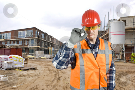 Saluting construction worker stock photo, A friendly looking construction worker touching his hard hat with is finger in salute of the customer by Corepics VOF