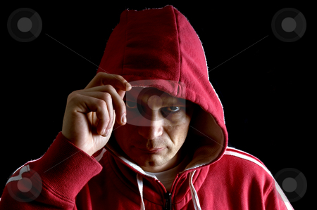 Hooligan stock photo, A grim looking hooligan, lifting his hood with his right arm, glaring at the camera. by Corepics VOF