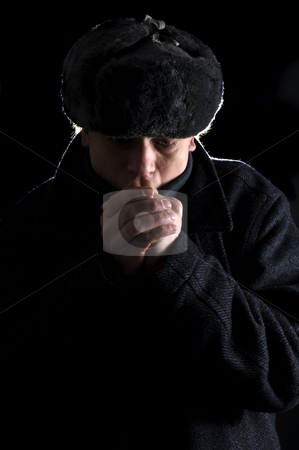 Cold hands stock photo, A man, dressed in Soviet attire, blowing in his cold hands by Corepics VOF