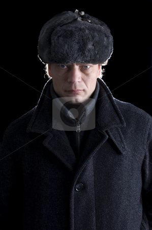 Man in winterclothes stock photo, A stern looking man with a fur cap and a woolen coat looking straight into the camera by Corepics VOF