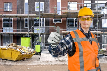 Satisfied construction worker stock photo, A satisfied looking construction worker giving a thumbs-up in front of a huge residential building site by Corepics VOF