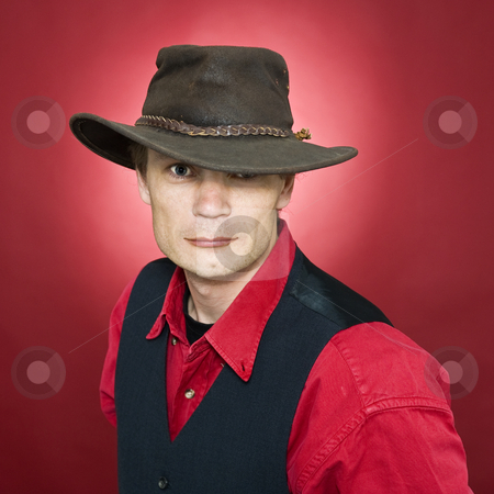 Man with leather hat stock photo, A man with a well worn leather head and a waistcoat by Corepics VOF