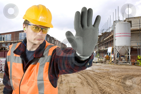 No trespassing stock photo, A serious looking construction worker giving a stop signal with his hand in front of a huge residential building site by Corepics VOF