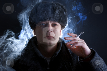 Smoking Soviet stock photo, A man, dressed in Soviet attire, smoking a cigarette, surrounded by smoke. by Corepics VOF