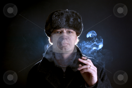 Smoking man stock photo, A man in his 30's, dressed as a former soviet, smoking a cigarette by Corepics VOF