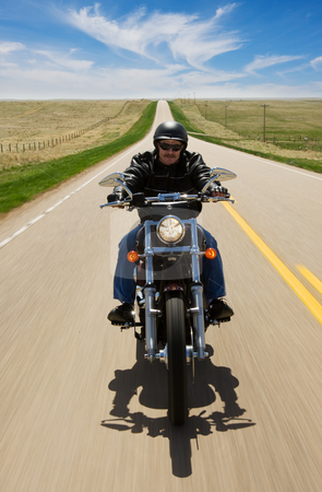 Motorcycle ride stock photo, A biker taking a ride on a long strait road by Steve Mcsweeny