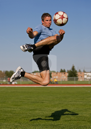Male soccer kick stock photo, Athletic male in the air kicking a soccer ball by Steve Mcsweeny