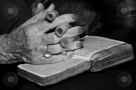Senior's hands in prayer stock photo, Senior's hands on old Bible in prayer by Steve Mcsweeny