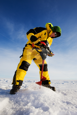 Winter fishing stock photo, Ice fisherman drilling a hole on a frozen lake with a power auger by Steve Mcsweeny