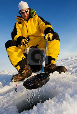 Winter fisherman stock photo, Ice fisherman cleaning ice from the hole with a ladle, focus on the scoop by Steve Mcsweeny