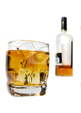 On the rocks stock photo, A glass of whiskey with bottle burred out in the background by Steve Mcsweeny
