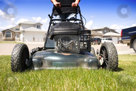 mowing the lawn stock photo, Close-up mowing the front lawn with houses in the background by Steve Mcsweeny