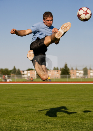 Male soccer stock photo, Athletic male in the air kicking a soccer ball by Steve Mcsweeny