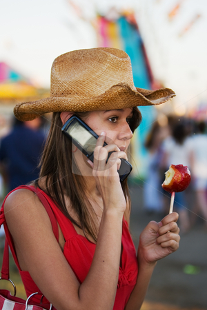 Teen at the carnival stock photo, A beautiful young woman talking on a cell phone with a candy apple in hand by Steve Mcsweeny