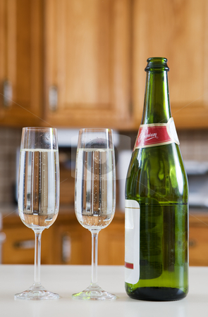Celebration at home stock photo, Champagne bottle and drinks in a modern kitchen by Steve Mcsweeny