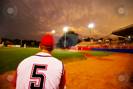 Evening baseball stock photo, Relief pitcher watching his team play baseball at night by Steve Mcsweeny