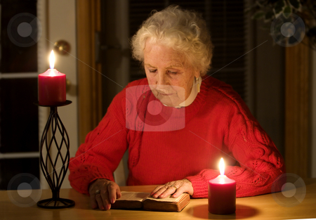 Elderly woman reading stock photo, Elderly lady sitting in candlelight reading the bible by Steve Mcsweeny