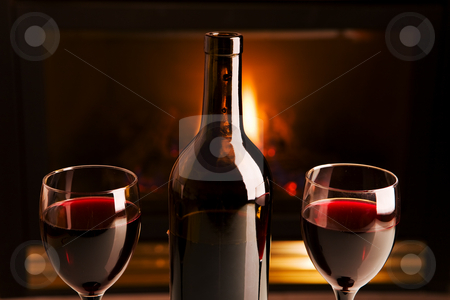 Wine and fireplace stock photo, A bottle of red wine and two glasses in front of a fireplace by Steve Mcsweeny