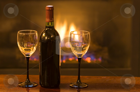 Cozy space stock photo, Bottle of wine with two empty glasses infront of a warm fire by Steve Mcsweeny