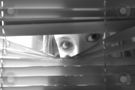 Who's out there stock photo, Young female looking through window blinds at night.(shallow depth of field) by Steve Mcsweeny