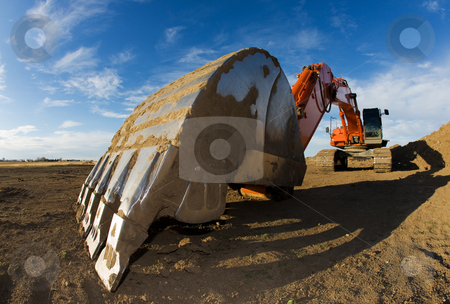 Orange backhoe stock photo, Orange backhoe parked at a construction site by Steve Mcsweeny
