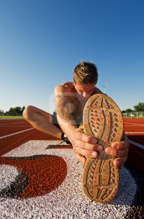 Male warmup stock photo, A male athlete stretching at the race track by Steve Mcsweeny