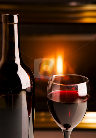Fireplace red wine stock photo, A bottle of red wine infront of a fireplace by Steve Mcsweeny
