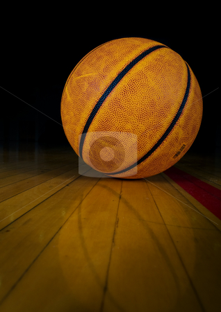 Basketball stock photo, A basketball on a dark gym floor with reflection by Steve Mcsweeny