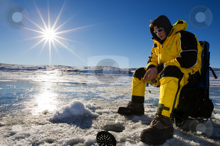 Sunny ice fishing stock photo, Fisherman enjoying a day on the ice on a bright sunny day by Steve Mcsweeny