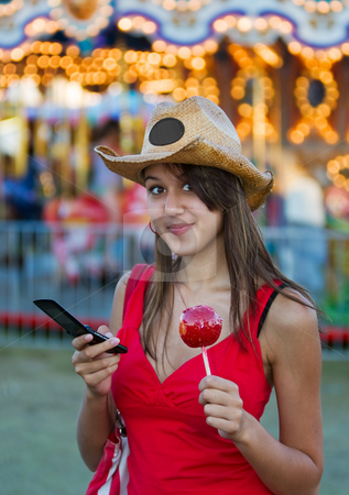 Candy apple girl stock photo, A pretty young woman at the fair with a candy apple and cellphone by Steve Mcsweeny