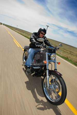 Biker ride stock photo, A biker taking a ride on a long strait rural road, tilted view by Steve Mcsweeny