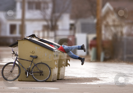 Urban poverty stock photo, Homeless man with a bike looking in a dumpster by Steve Mcsweeny