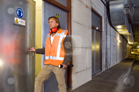 Tunnel Engineer stock photo, A sturdy looking engineer, opening a door to an engine room in a dimly lit tram tunnel, ignoring the safety precaution to wear his ear protection by Corepics VOF