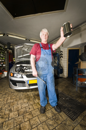 Motor Mechanic stock photo, A car mechanic holding up a blank tin with a wrench in his hands posing in front of the car he's been working on inside a small garage by Corepics VOF
