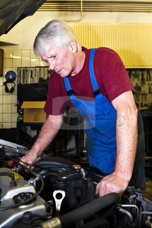 Motor mechanic stock photo, A senior motor mechanic servicing a car inside a garage by Corepics VOF