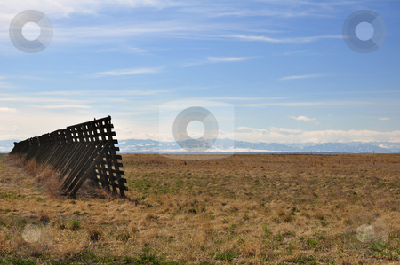 Snow Fence and Rocky Mountains stock photo, A snow barrier stands in an empty field in Colorado with the Rocky Mountains in the distance. by Ben O'Neal