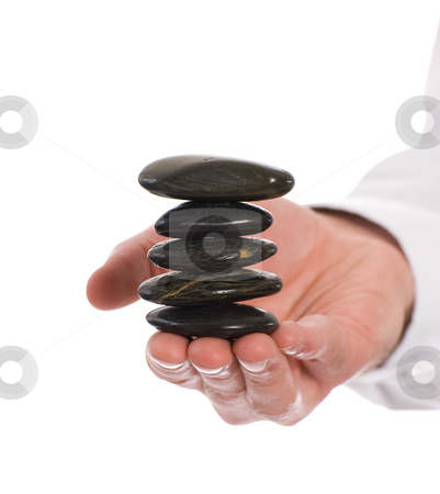 Meditation Rocks stock photo, A stack of meditation river rocks being held carefully by a meditating person, isolated against a white background by Richard Nelson