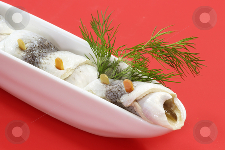 Rolled herring stock photo, Rolled herring in a bowl on red background by Birgit Reitz-Hofmann
