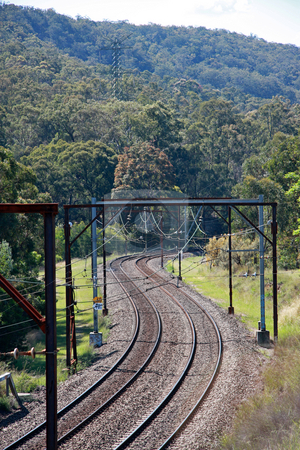 Mountain rail pass stock photo, A pair of parallel snaking railway tracks ascending through a thickly forested mountain pass. by Adam Goss