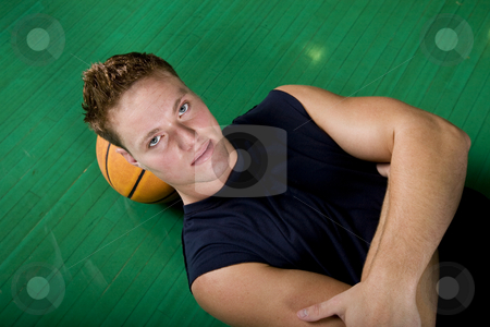 Resting Basketball Player stock photo, A young basketball player resting on the court. by Brenda Carson