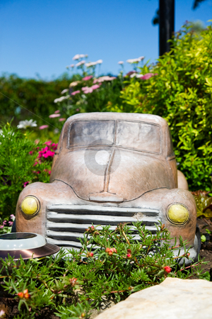 Truck in Flower Bed stock photo, An old truck ornament in a lush, sunny, flower bed.  Shallow depth of field.  Focus on front of truck. by Brenda Carson