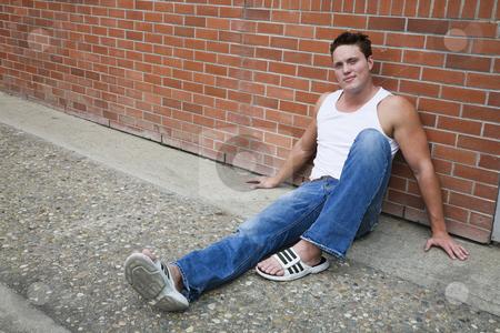 Urban Man stock photo, A young man sitting on a sidewalk , leaning against a brick wall. by Brenda Carson