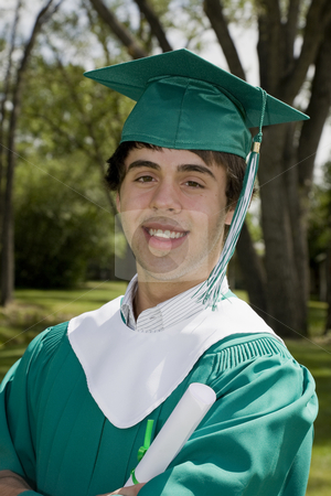 Smiling Graduate Boy stock photo, A happy young graduate, smiling & proudly holding his degree. by Brenda Carson